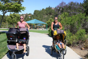 Two moms going for a walk pushing their children in strollers on a sunny day