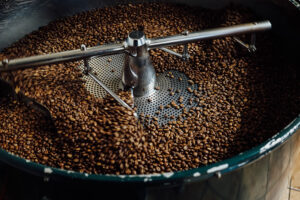 Close-up image of metal coffee roaster roasting brown coffee beans