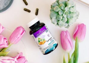 bottle of New Chapter Sleep supplement with capsules spilling out on white surface with pink tulips and blue hydrangea