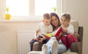 Mother reading book in comfy chair with son and daughter with sunny window in background