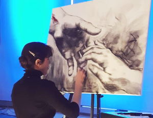 Profile of young female artist sketching on canvas with black charcoal.