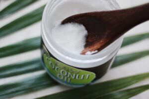 wooden spoon in open glass jar of coconut oil on striped tablecloth