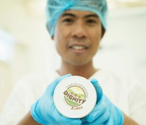 smiling factory worker wearing blue hair net and gloves holding glass jar of coconut oil