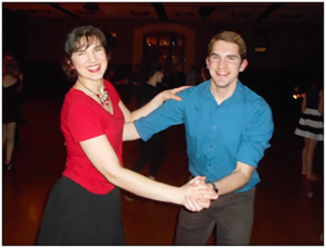 Young woman in red dancing with young man in blue on black background